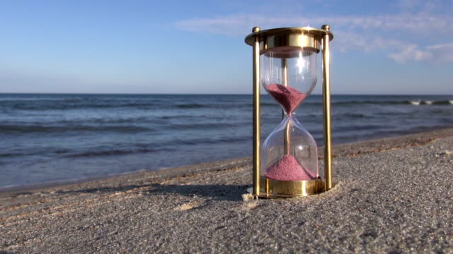 Hourglass with pink sand by the sea video