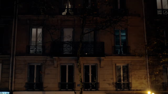 House at night with some people in the windows, Paris PARIS, FRANCE - SEPTEMBER 29, 2017: Exterior of a house, view at night in dim light of the lantern. People can be seen in the windows facade stock videos & royalty-free footage