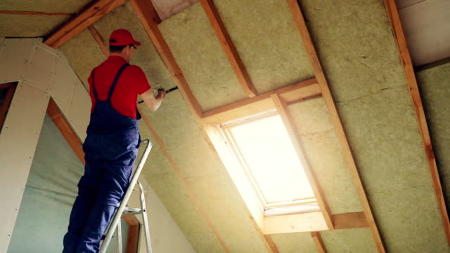 house attic insulation - construction worker installing rock wool in mansard wall - soffitto video stock e b–roll