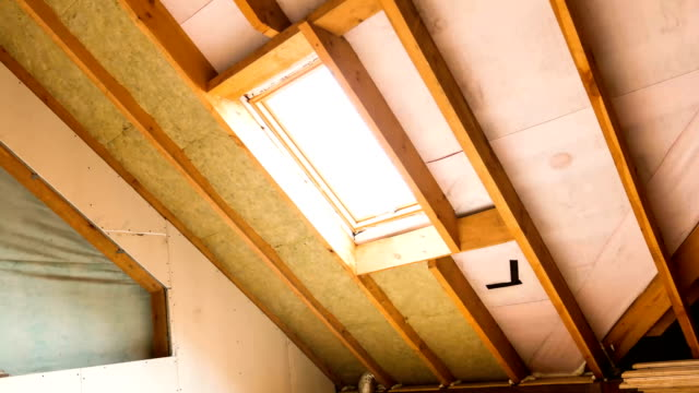 house attic under construction mansard wall insulation with rock wool - soffitto video stock e b–roll