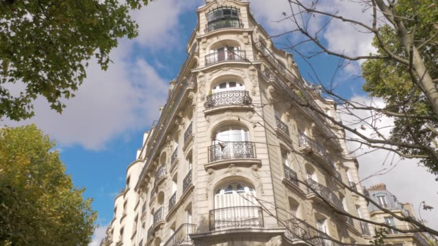 House baroque exterior and autumn trees in Paris, France Low angle shot of the building in baroque architecture style, sun shining and reflecting in the windows, following view to the autumn trees. Paris, France french architecture stock videos & royalty-free footage