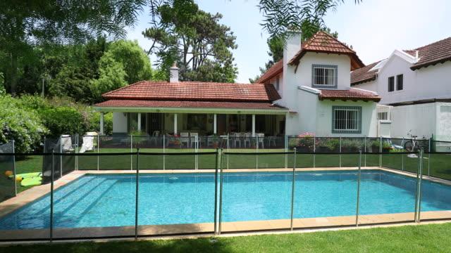 vídeos de stock e filmes b-roll de house exterior during sunny day. residential home with swimming pool - cercado