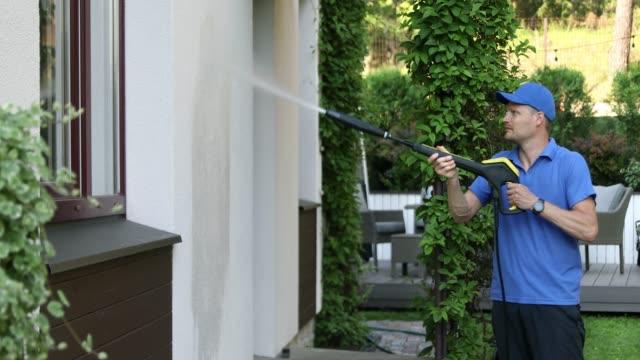 hausfassadenreinigungsservice. mann waschen stuckwand mit hochdruckreiniger - waschmaschine wand stock-videos und b-roll-filmmaterial