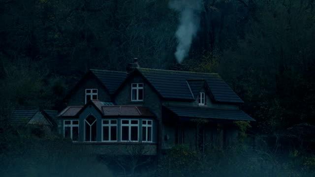 stockvideo's en b-roll-footage met huis in het bos op bleak misty day - schoorsteen