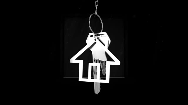 House keys and key fob hanging over door opening in the background Animation of silver house keys and house shaped key fob hanging over a door opening in the background home icon stock videos & royalty-free footage