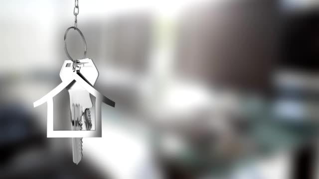 hausschlüssel und schlüsselanhänger hängen aus fokus hintergrund 4k - hypothek stock-videos und b-roll-filmmaterial