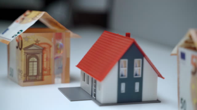 House mortgage concept, home loan for real estate. Financial investment in buying property, housing and construction plans and projects prepared for rich customers. Miniature house models made of colorful plastic and euro banknotes. Money for buying house