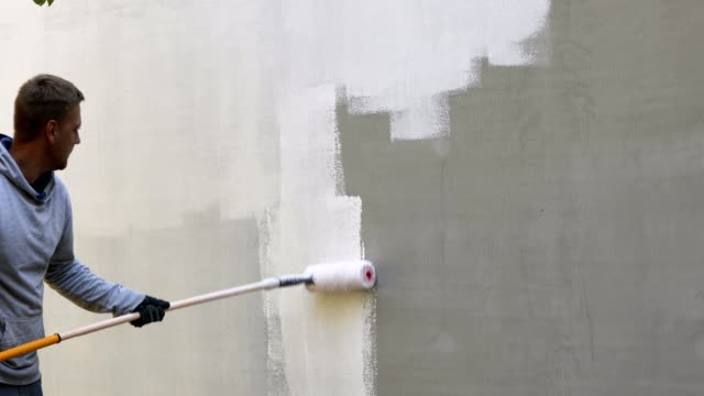 house painter painting building exterior with roller house painter painting building exterior with roller house painter stock videos & royalty-free footage