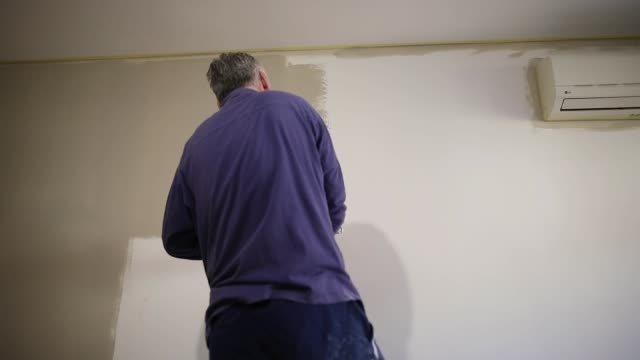 House painter painting residential home interior in gray color with paint roller House painter painting residential home interior in gray color with paint roller house painter stock videos & royalty-free footage
