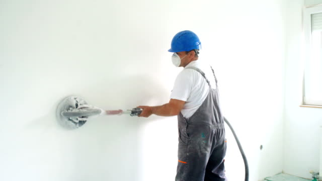 House painter sanding walls before painting. Closeup rear view of a handyman using an electric sander to polish the surface of the wall before painting. house painter stock videos & royalty-free footage