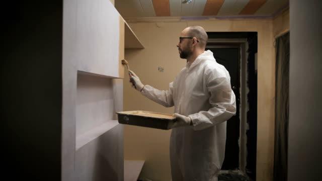 stockvideo's en b-roll-footage met huisschilder met glazen en baard roller verf de muur - alleen één mid volwassen man