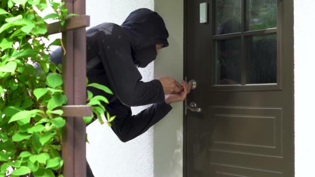house robbery - robber break door lock and entering building - вор стоковые видео и кадры b-roll