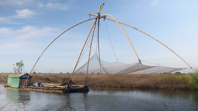 Houseboat and chinese fishing net on a lake: Windy day