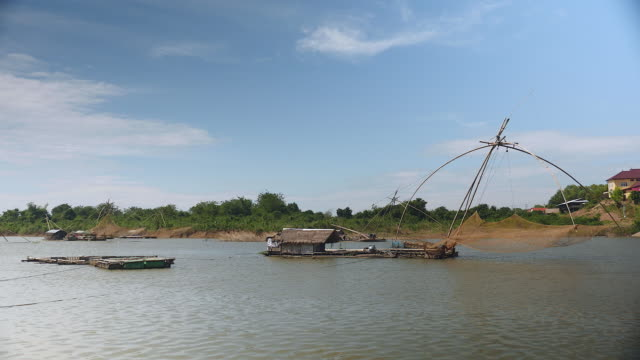 Houseboats with chinese fishing nets on a lake with bamboo fish cages for rearing fish