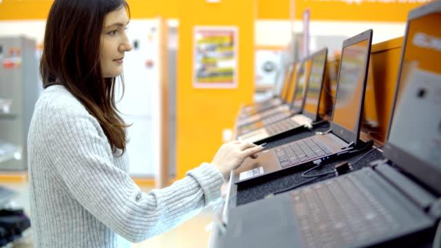 vídeos y material grabado en eventos de stock de tienda de electrodomésticos. mujer joven elige un ordenador portátil - electrónica