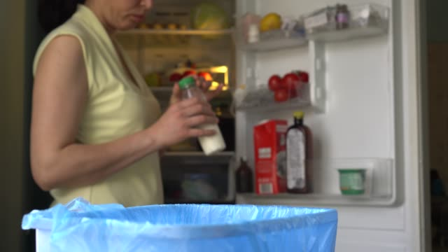 household food and drink waste in the garbage. woman, kitchen, fridge - obsoleto video stock e b–roll