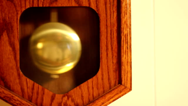 Household Wall Clock Close-up of the pendulum of a household wall clock. wall clock stock videos & royalty-free footage