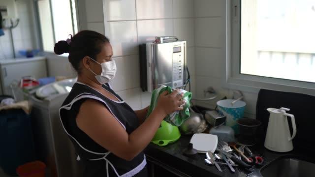 stockvideo's en b-roll-footage met huishoudster die de schotels wast die beschermend masker dragen - mid volwassen vrouw