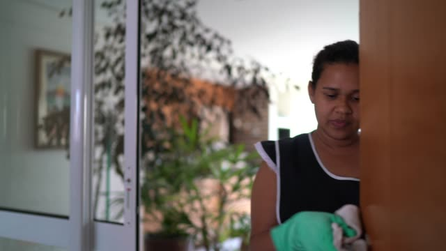Housekeeper with glove cleaning the house