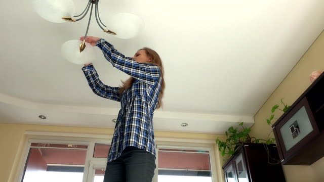 housekeeper woman climb up and change light bulbs in chandelier. video