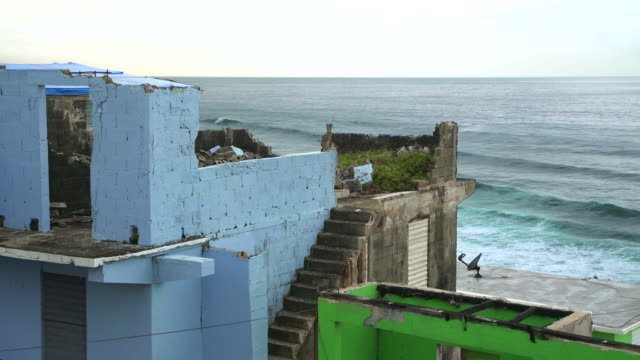Houses damaged by Hurricane Maria in La Perla, San Juan, Puerto Rico Damaged houses from Hurricane Maria in La Perla, Old San Juan, Puerto Rico with ocean waves beyond. puerto rico stock videos & royalty-free footage