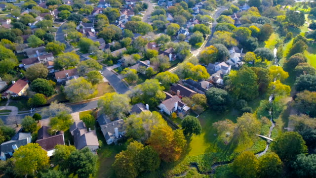 houses , homes , neighborhood community under golden morning sunlight - edificio residenziale video stock e b–roll