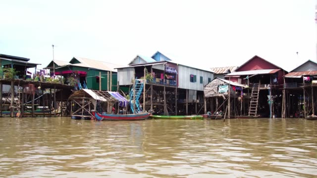 Houses on stilts in Tonle Sap floating village in Siem Reap, Cambodia. Popular boat tour trip for backpackers & tourists in Cambodia. Tonle Sap floating village canoe tour. Woman rows a boat through flooded mangrove forest. Taxi boats for tourists. lake in Siem Reap, Cambodia. southeast stock videos & royalty-free footage
