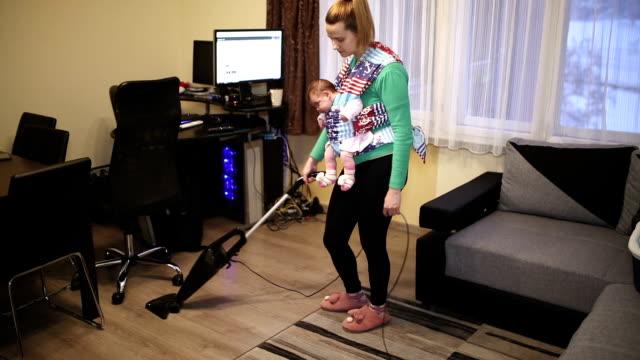 ev hanımı taşımak bebek oda elektrikli süpürge ile temizlik sırasında - ev temizleme stok videoları ve detay görüntü çekimi