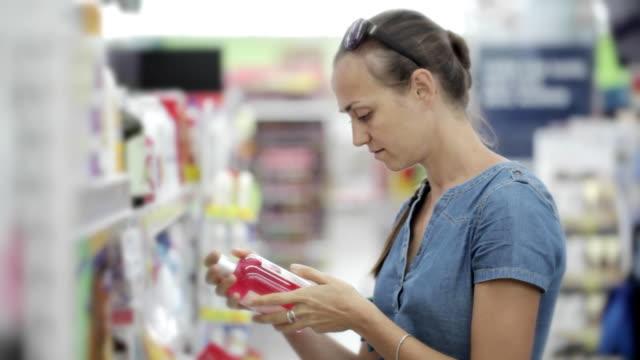 hausfrau, körper-produkte im supermarkt zu wählen. - etikett stock-videos und b-roll-filmmaterial
