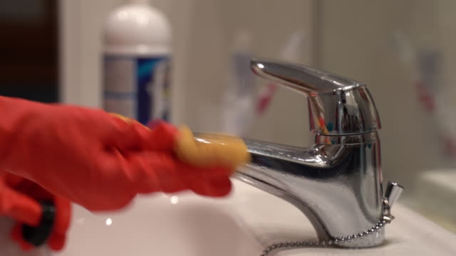 housewife in protective rubber orange gloves cleaning stainless water tap with yellow sponge and detergent gel. dirty bathroom faucet, household chemicals, hygiene, sanitation and house cleaning - bleach stock videos & royalty-free footage