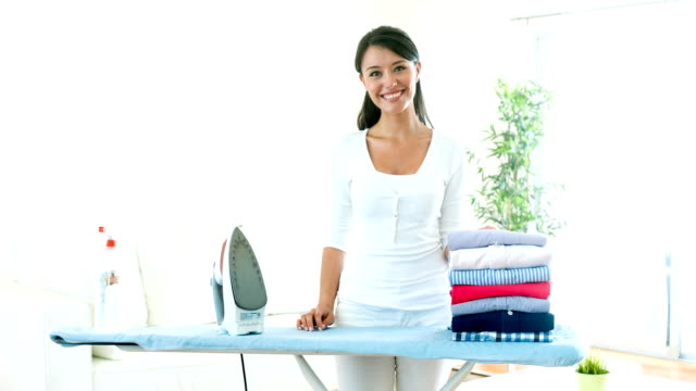 Housewife ironing clothes at home video