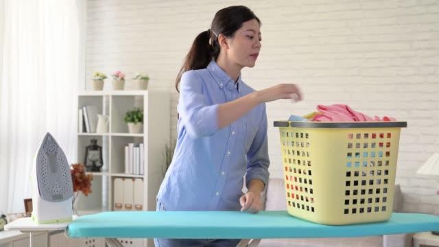 リビング ルームで家族の服をアイロンの主婦 - 楽しい 洗濯点の映像素材/bロール