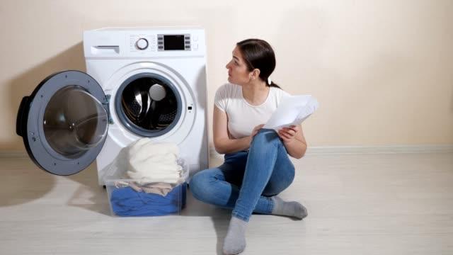 hausfrau erfährt einstellungen der neuen waschmaschine auf dem boden - waschmaschine wand stock-videos und b-roll-filmmaterial