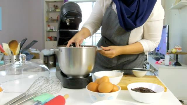 vidéos et rushes de femme au foyer, mélanger les ingrédients du gâteau à la maison - batteur électrique