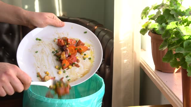 Housewife throws baked vegetables in the trash