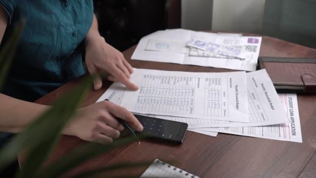 en hemmafru kvinna registrerar och spårar alla månatliga familjekostnader på papper - accounting bildbanksvideor och videomaterial från bakom kulisserna