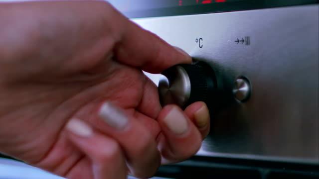 vidéos et rushes de femme au foyer de travail avec un four - température