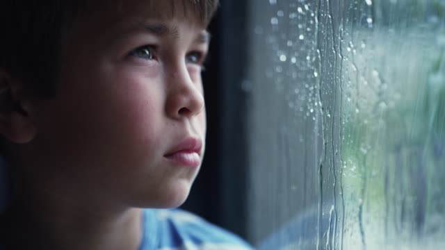 How long is it going to rain? 4k video footage of a sad young boy watching the rain through a window at home one boy only stock videos & royalty-free footage