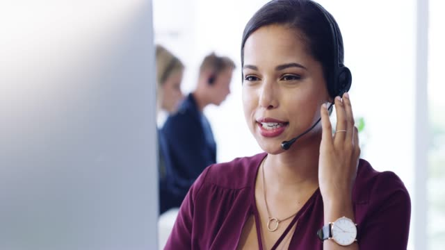 How may I assist you? 4k video footage of an attractive young female customer service agent working in the office call centre videos stock videos & royalty-free footage