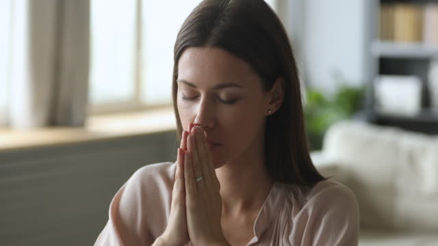 Сhristian young woman saying prayer with eyes closed at home