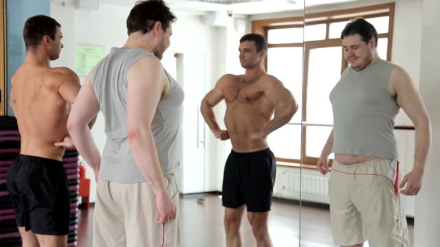hubby man and athlete bodybuilder look at themselves in the mirror in the gym video
