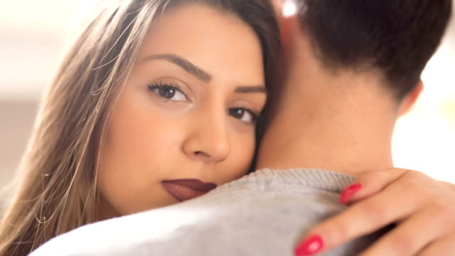 Hug Me Tight! Close-up of a beautiful young woman in love, cuddling on a man's shoulder. human joint stock videos & royalty-free footage