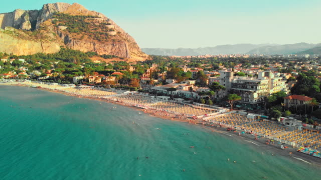 palermo, sicily, italy - august 2019: huge beach on the ocean. people swim and sunbathe. against the background of a city with a lot of trees and plants. rocky mountains. symmetric umbrellas on the beach. sunset time. aerial drone shot - sicily filmów i materiałów b-roll