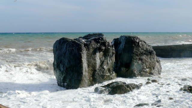 Huge boulders on beach during storm, close-up video