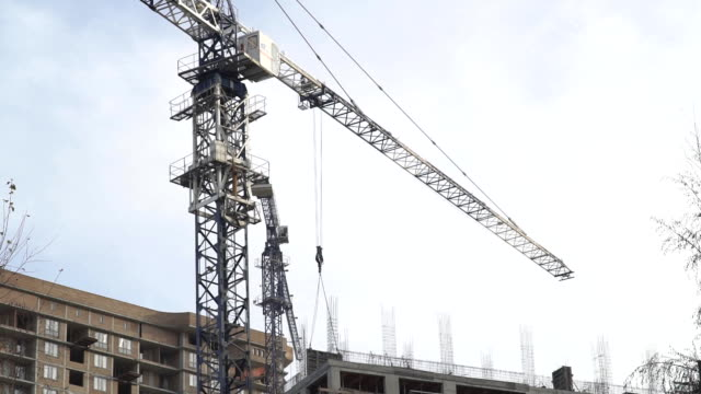 Huge crane rising between building under construction video
