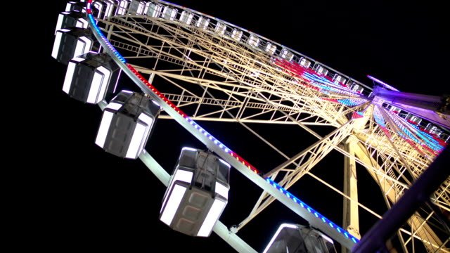 Huge Ferris wheel with illuminated passenger cars rotating fast, amusement ride video