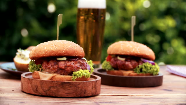 Huge gourmet cheese burgers on a rustic wooden table outdoors video
