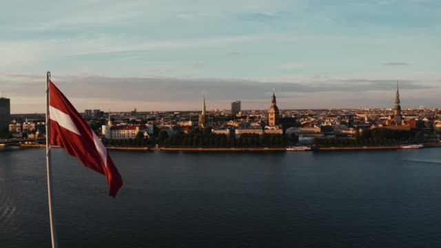 huge latvian flag flutters on wind with riga old town in the background - estonia filmów i materiałów b-roll