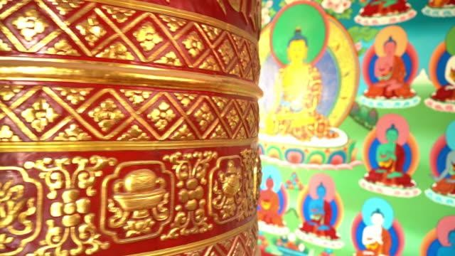 Huge Ornate gold gilded Tibetan prayer wheel spinning in the monastery in Kathmandu, Nepal.