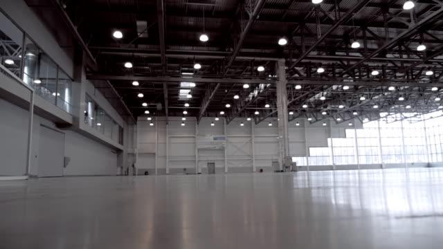 vídeos de stock e filmes b-roll de huge, spacious hangar with large windows, lit by lots of lamps - armazém